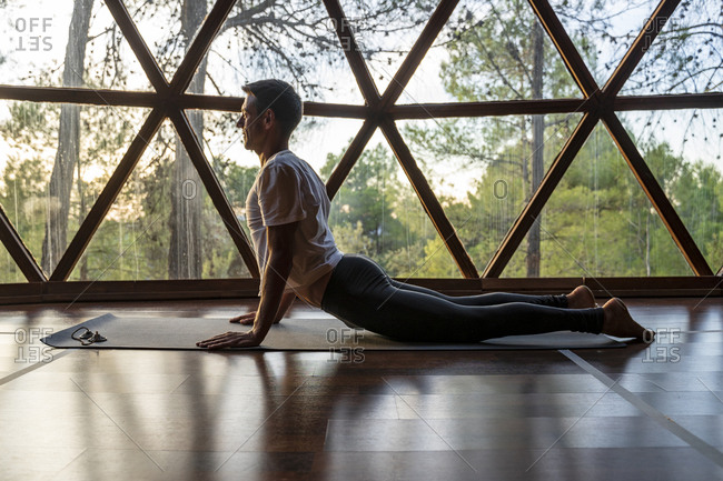 Mature man practicing yoga on mat at health spa