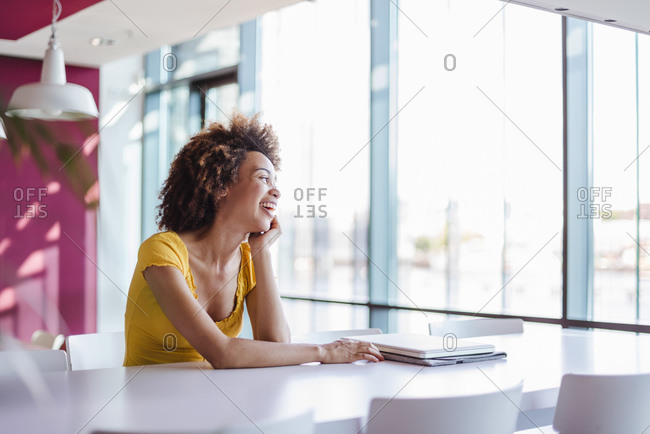 Young woman working in modern office- laughing