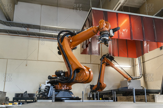 Orange robotic arms manufacturing in industry