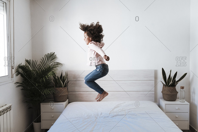 Cute girl jumping on bed in bedroom at home
