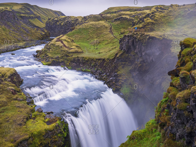 Scenic view of waterfall on green landscape