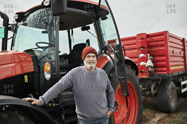 Farmer standing by tractor at soybean farm
