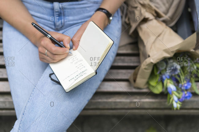 Woman writing in note pad sitting on bench