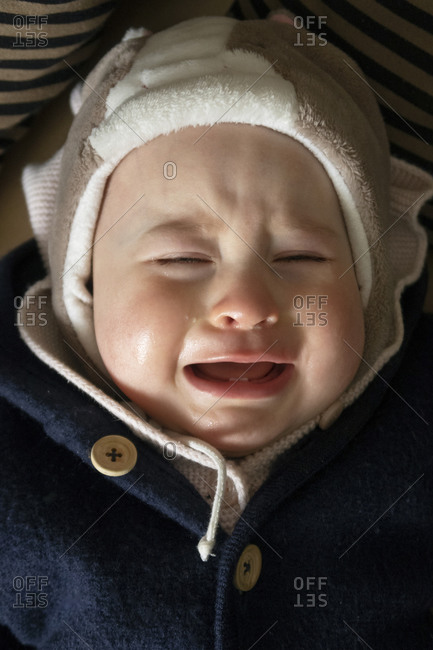 Baby girl crying while lying down in house