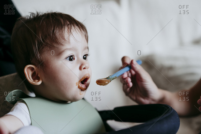 Mother's hand feeding baby boy at home