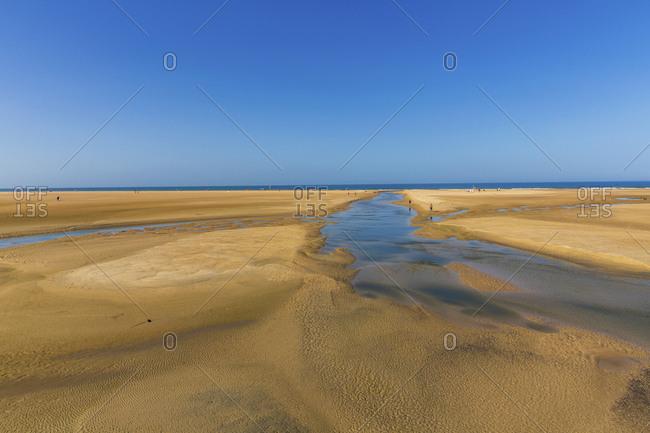 Clear blue sky over vast sandy beach