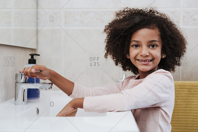 Smiling girl washing hands at home