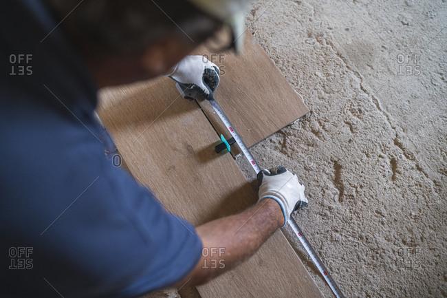 Mature man measuring parquet floor