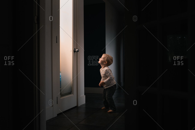 Toddler looking at frosted glass of illuminated pantry while searching for a late night snack