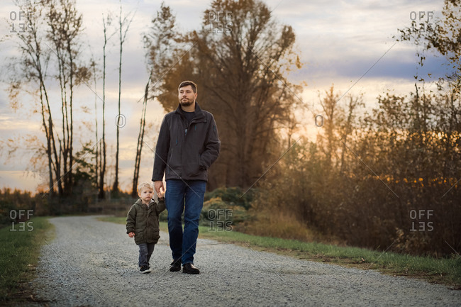 Man walking hand in hand on a gravel path with his toddler son