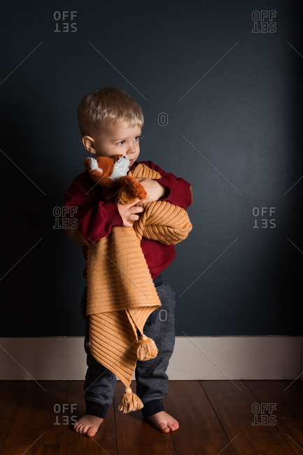 Toddler boy holding a stuffed fox and yellow blanket