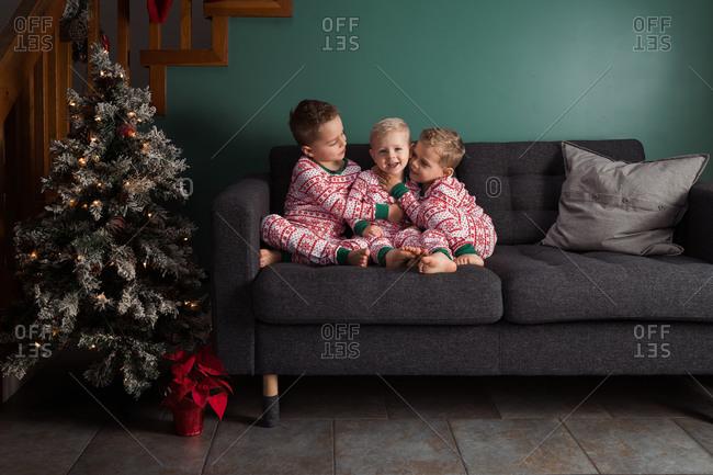 Three little boys cuddling on sofa by Christmas tree in their pajamas