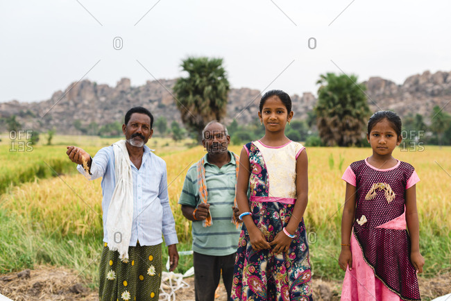 Hampi, Karnataka, India - April 06, 2019: Portrait of two Indian girls close to proud rice farmer family showing the harvest