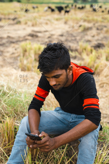 Hampi, Karnataka, India - April 06, 2019: Young Indian farmer chatting with mobile phone after harvest