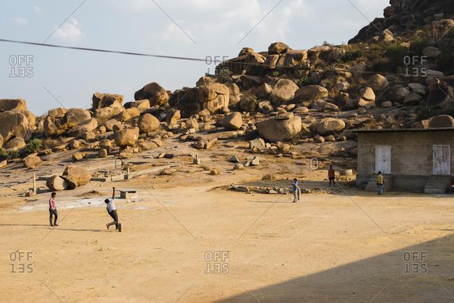 Hampi, Karnataka, India - April 07, 2019: Group of Indian people playing Cricket in abandoned school in Hampi Island