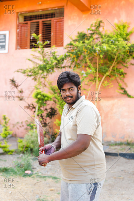 Hampi, Karnataka, India - April 07, 2019: Indian young male holding Cricket paddle in front of an abandoned school in Hampi Island