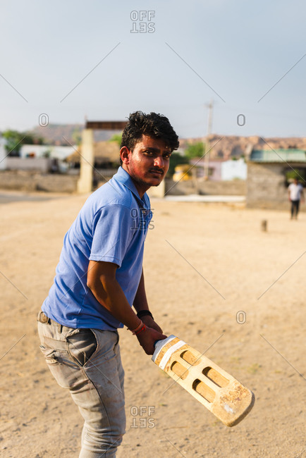 Hampi, Karnataka, India - April 07, 2019: Indian young male holding Cricket paddle in an abandoned school field in Hampi Island