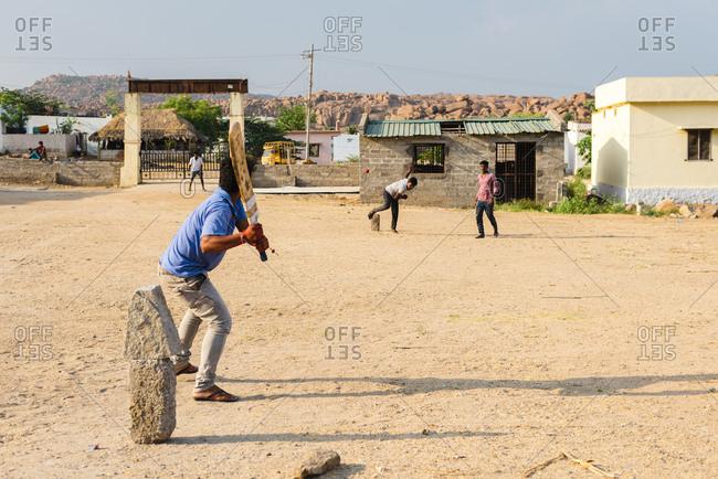 Hampi, Karnataka, India - April 07, 2019: Young Indian man ready to hit cricket ball