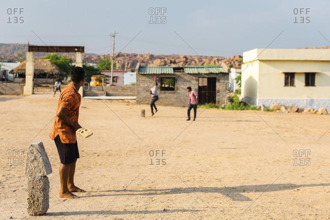 Hampi, Karnataka, India - April 07, 2019: Young Indian man preparing to a hit cricket ball