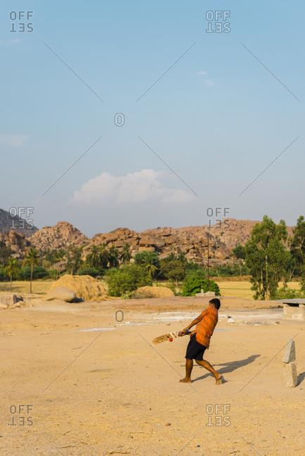 Hampi, Karnataka, India - April 07, 2019: Young Indian man hitting a cricket ball