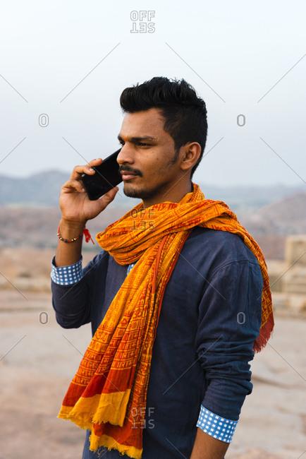 Hampi, Karnataka, India - April 08, 2019: Confident Indian male talking by mobile phone wearing traditional orange scarf
