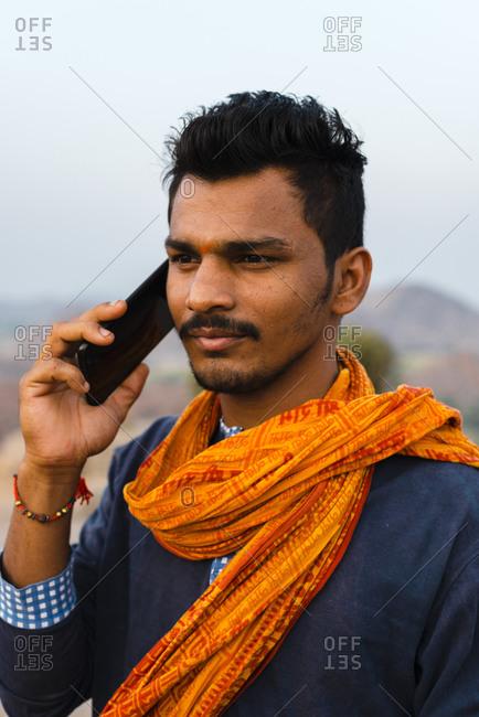 Hampi, Karnataka, India - April 08, 2019: Modern Indian male talking by mobile phone wearing traditional orange scarf