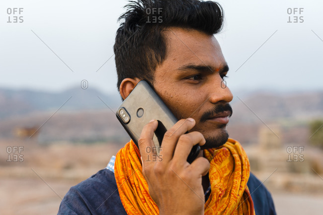 Hampi, Karnataka, India - April 08, 2019: Modern Indian male talking by mobile phone wearing traditional orange scarf looking away