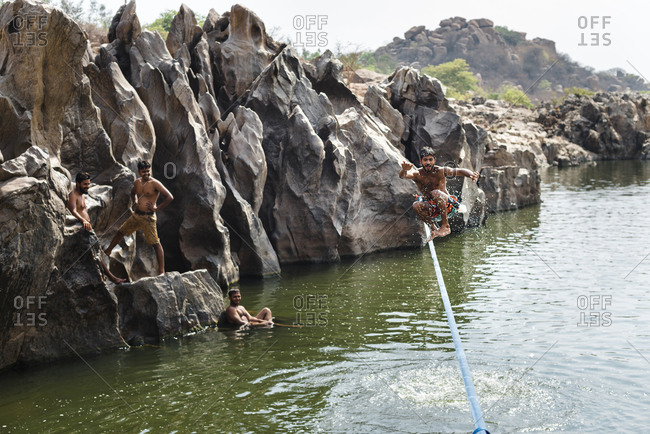 Hampi, Karnataka, India - April 09, 2019: Acrobatic smiling Indian male jumping on tightrope balancing on the waters of a river as friends watch