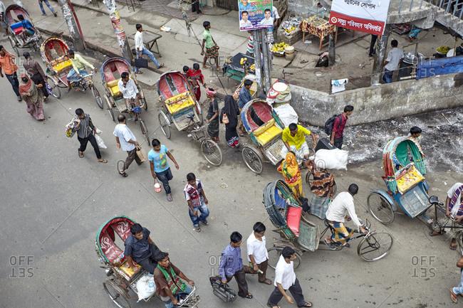 Dhaka, Bangladesh - April 28, 2013: High angle view of a street full of colorful rickshaws in downtown Dhaka