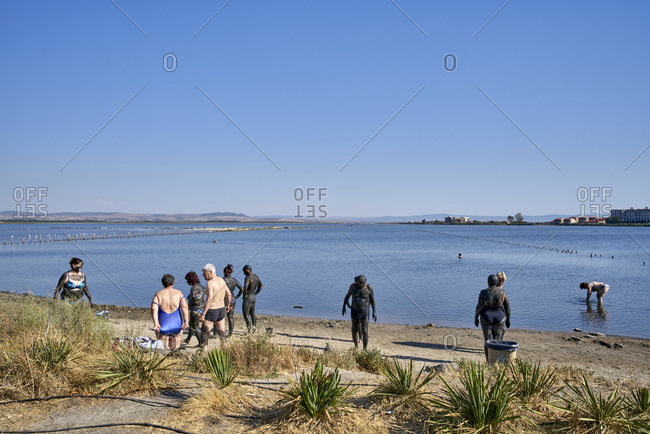 Pomorie, Bulgaria - August 11, 2020: Tourists covered in mud on beach at Pomorie Lake coastal lagoon