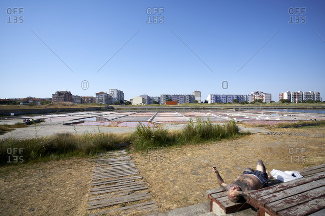 Pomorie, Bulgaria - August 11, 2020: Man resting on outdoor wooden table by Pomorie Lake with artificial salt lakes and ponds