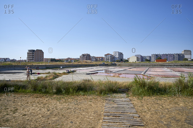 Pomorie, Bulgaria - August 11, 2020: Tourists applying mud to their skin by Pomorie Lake with artificial salt lakes and ponds