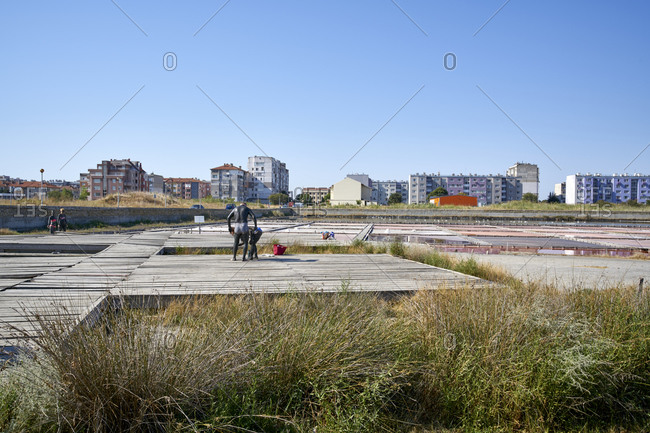 Pomorie, Bulgaria - August 11, 2020: Tourists applying clay to their skin by Pomorie Lake with artificial salt lakes and ponds