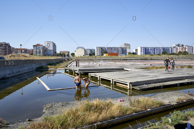 Pomorie, Bulgaria - August 11, 2020: Tourists bathing and applying clay to their skin at the artificial salt lakes and ponds at Pomorie Lake