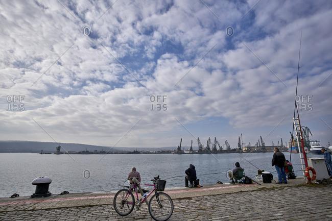 Varna, Bulgaria - November 16, 2020: Fisherman relax on promenade along the Black Sea Coast