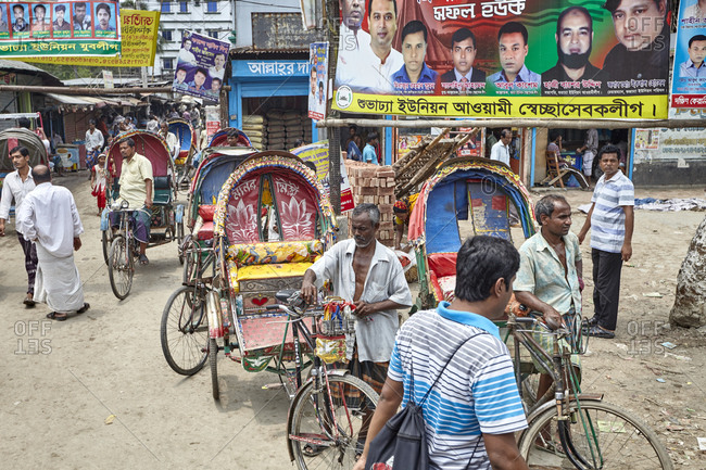 Dhaka, Bangladesh - April 26, 2013: A line of rickshaws with drivers waiting for business in the streets of Dhaka