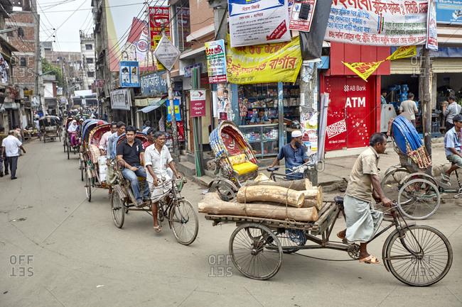 Dhaka, Bangladesh - April 26, 2013: A lot of colorful rickshaws on a busy street in downtown Dhaka