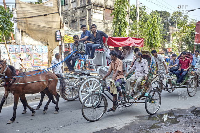 Dhaka, Bangladesh - April 28, 2013: Horse-Drawn Carriage on a busy street in the old quarter of Dhaka carrying passengers