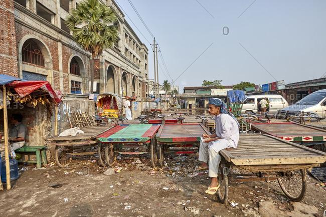Dhaka, Bangladesh - April 27, 2013: A boy sitting on a cargo rickshaw on a street in downtown Dhaka eating a snack