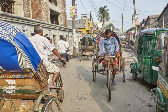 Dhaka, Bangladesh - April 27, 2013: Many rickshaw drivers working on the streets in city of Dhaka