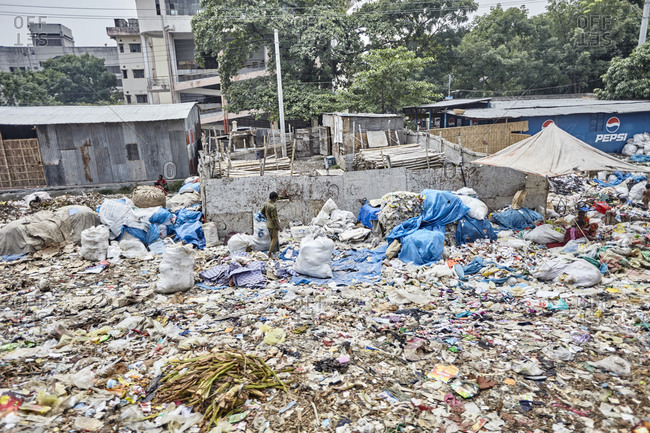 Dhaka, Bangladesh - April 28, 2013: People collecting useful things from a garbage dump in a slum area in Dhaka
