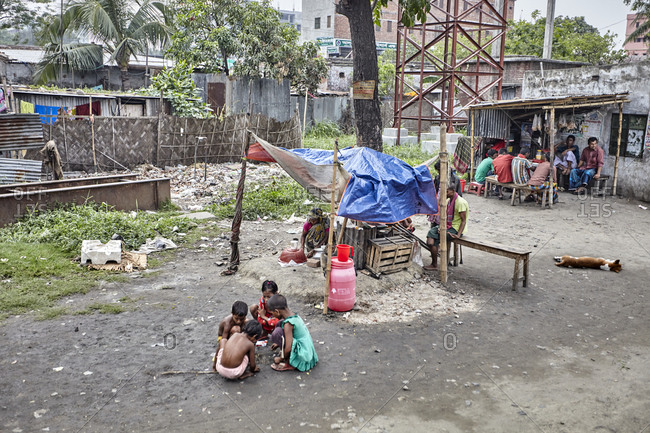 Dhaka, Bangladesh - April 28, 2013: Slum-dwellers in a slum near Dhaka including young children playing in the dirt