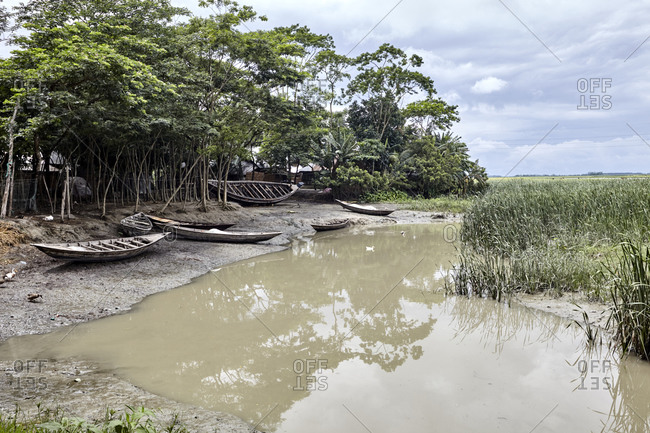 Fishing boats beached on a river shore in a small rural village, Chandra Mohan, Barisal, Bangladesh