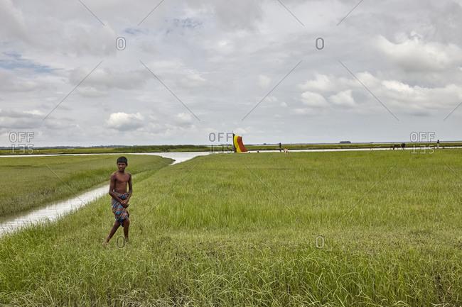 Chandra Mohan, Barisal, Bangladesh - May 15, 2013: A boy walking on a rice field in rural Bangladesh