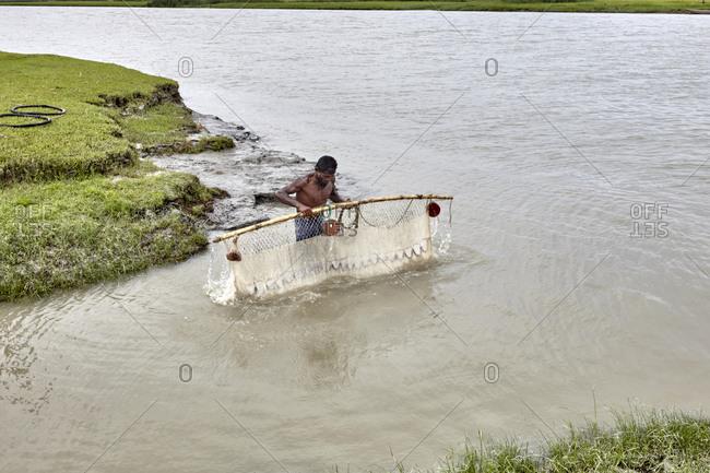 Chandra Mohan, Barisal, Bangladesh - May 15, 2013: A fisherman pulling his fishing net out of the river in rural Bangladesh