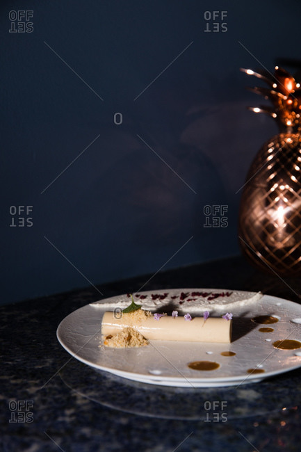 A decadent gourmet dessert served on a plate in front of dark blue background beside a copper pineapple