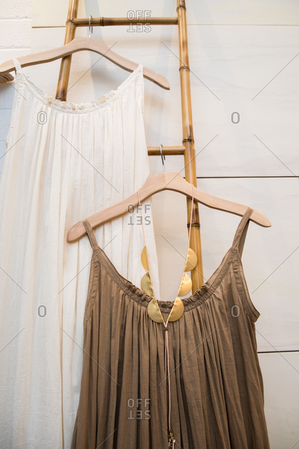 Boho style dresses hanging on hangers on a bamboo ladder in a boutique