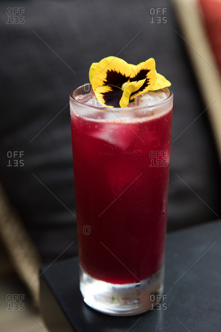 Fruity cocktail garnished with a yellow flower