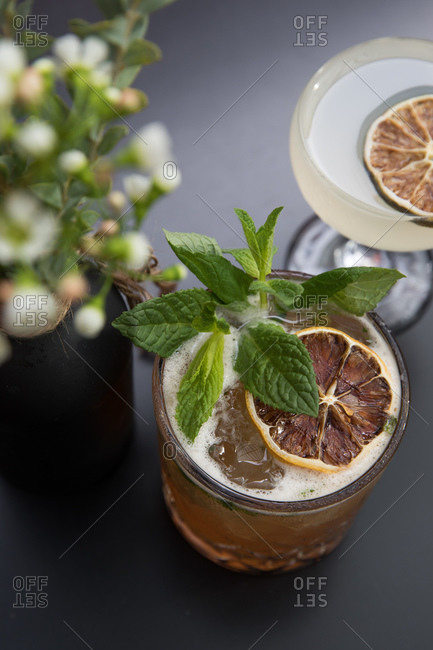 Overhead view of a cocktail in glasses garnished with citrus fruit slices and mint