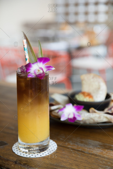 A mai tai cocktail served with an orchid garnish in a restaurant